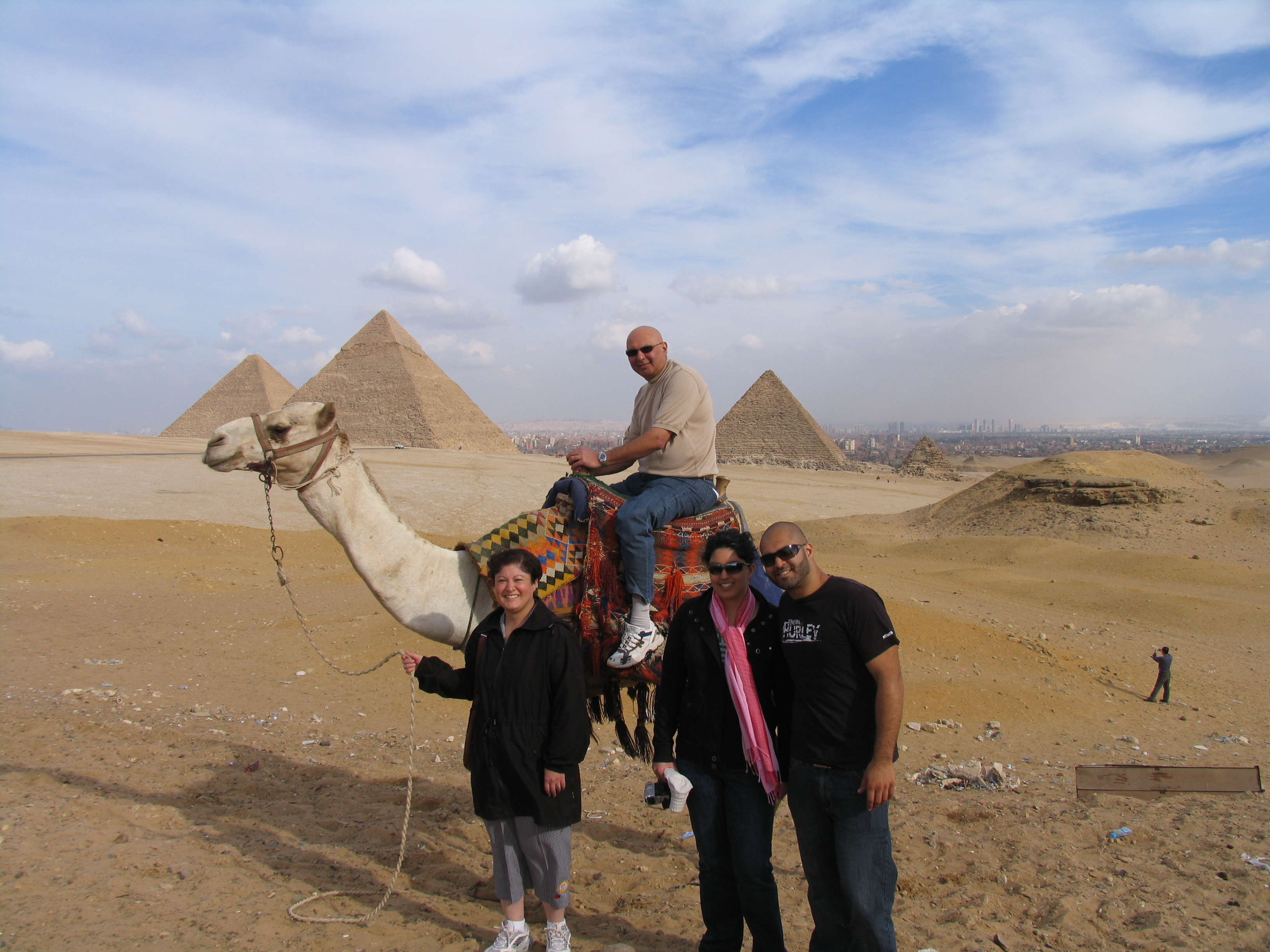 The picture shows Noorali on the camel at the Giza pyramids with Sabiya, Alia and Hussein in the foreground.