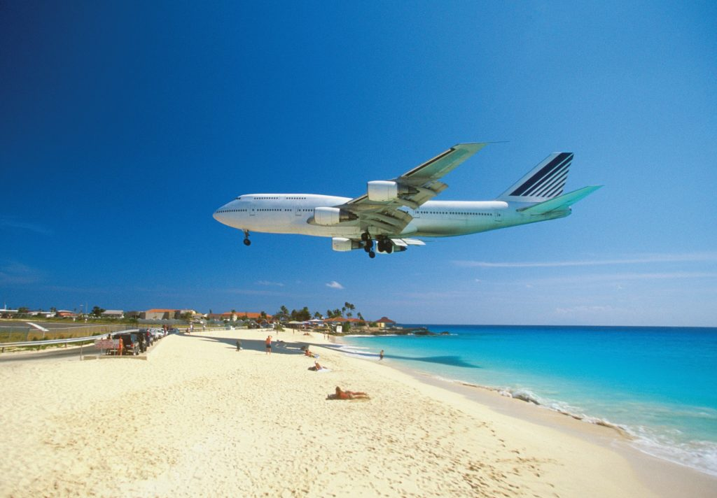 A plane coming in for landing on Maho Bay Beach, Saint Martin, Caribbean. (Photodisc/Thinkstock)