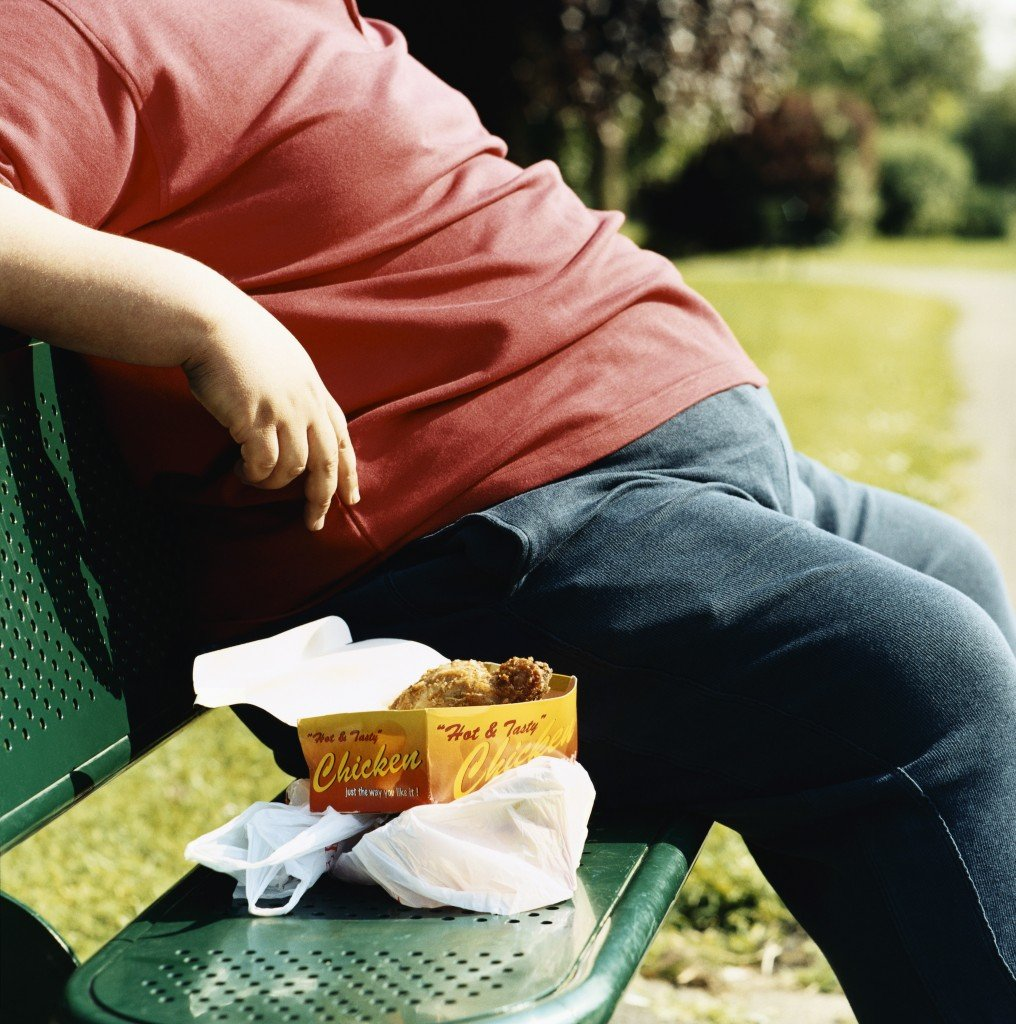 An overweight man sitting on a bench with take-out food. (Digital Vision/Thinkstock)
