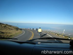 The bikers riding down the mountain road under the watchful eyes of Sabiya and Noorali in the van - drinking coffee and taking pictures.