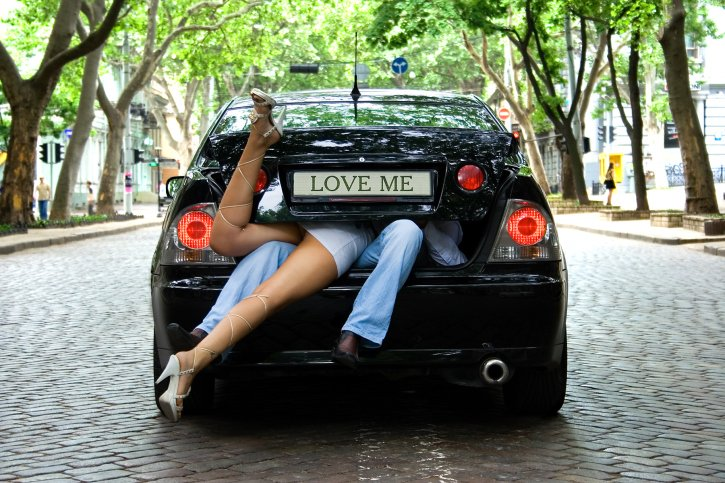 A couple taking a funny picture with their car. (iStockphoto)