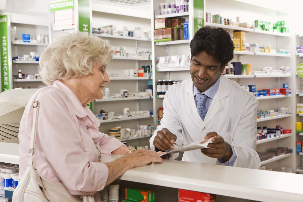 A senior citizen reviewing her medication with a pharmacist. (Getty Images)