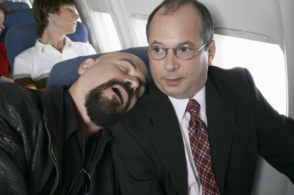 A businessman trapped in his seat by a sleeping passenger. (Digital Vision)